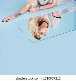 Beautiful woman lie down on mirror reflection floor, studio lighting aqua color backgrounds, copy space for text logo. Reflection of our mind and soul concept. surreal image