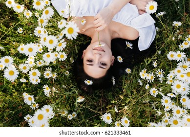 The beautiful woman lies in the field of chamomiles