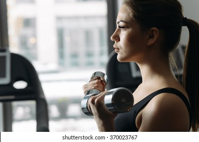Beautiful woman lifting dumbbell in gym. She training biceps.