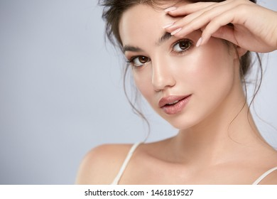 beautiful woman with light make-up and golden shadow looking to the camera, girl with healthy skin and big eyes