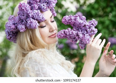 Beautiful woman with lilac flower wreath. Girl in a wreath of lilac in the spring.  Lilac wreath. Lilac. Gardening. Series.