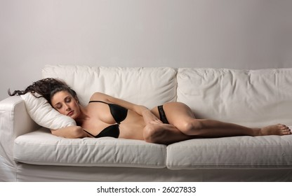 a beautiful woman in lingerie relaxing on a sofa