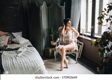 Beautiful woman in lingerie showing long legs sexy pose sitting at chair over her bedroom with big window, flowers. Sexual memories. Bride boudoir. Wedding morning.