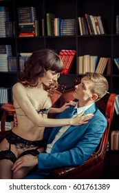 Beautiful woman in lingerie trying to seduce a businessman. Passion and calm contrast. Lovers concept