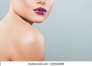 Beautiful woman lips with purple glossy lipstick and lipgloss on background with copy space
