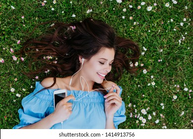 Beautiful woman listening to music with headphones and lying in a garden of flowers