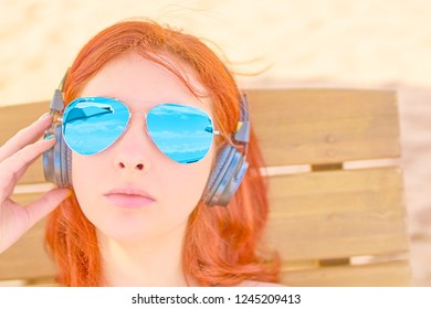 Beautiful woman listening to music on the beach. Portrait of a red-haired girl resting on the beach, lying on a deck chair and listening to relaxing music.
