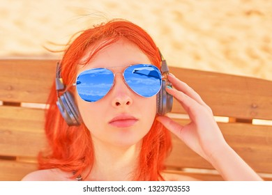 Beautiful woman listening to music on the beach. Portrait of a red-haired woman in sunglasses resting on the beach, lying on a longer and listening to relaxing melody.