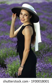 beautiful woman in little black dress and wide hat resting on the lavender field Provence elegance