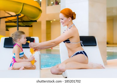 beautiful woman with little girl near pool have a rest