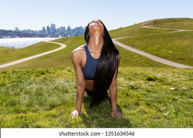 Beautiful woman with long black hair wearing yoga pants and spor
