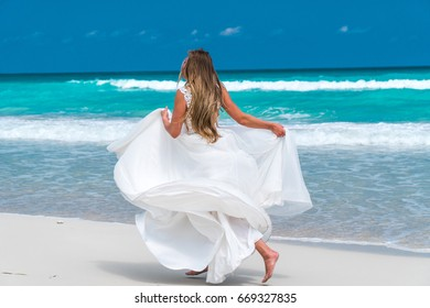Beautiful woman with long blond hair dressed in white wedding dress is running a back on the sand of Caribbean sea coastline