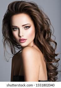 Schöne Frau mit langbraunem Haar. Porträt eines sinnlichen erwachsenen Mädchens mit lockigem Haar.