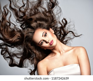 Beautiful  woman with long brown curly hair. Portrait of a pretty young  girl with flying hair