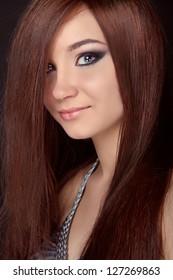 Beautiful woman with long brown hair. Closeup portrait of fashion model posing at studio.