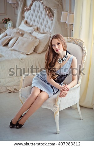 badd7e84077f Beautiful woman with long brown hair in grey dress in the interior sitting  in armchair
