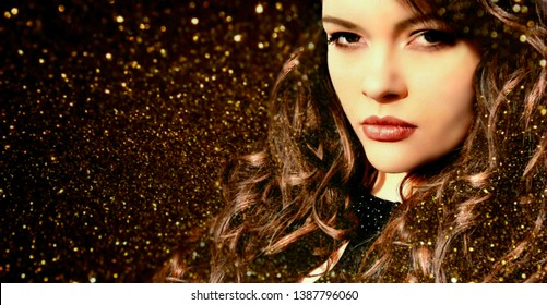 Beautiful woman with long curly hair and make-up in brown colors over golden sparkling background