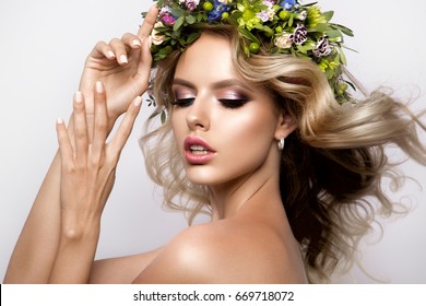 Beautiful Woman with Long Curly Hair, Perfect Makeup and Wreath of Spring Flowers