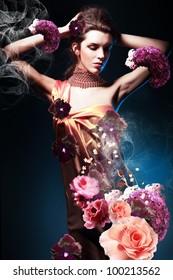 beautiful woman in long dress in blue light with flowers