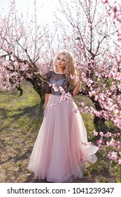 Beautiful woman in a long dress, in the garden of blooming peaches