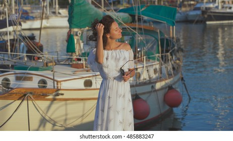 Beautiful woman in the long dress on a pier at a summer day. Enjoying the view at a port. Cyprus. Freedom