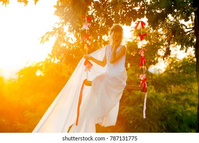 Beautiful woman in a long dress on a swing in the sunset