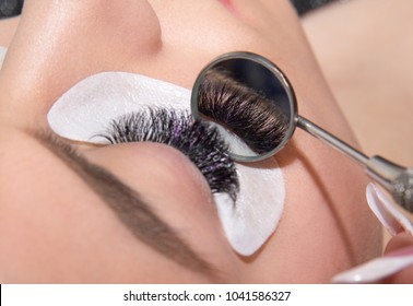 Beautiful woman with long eyelashes in a beauty salon eyelash extension procedure lashes close up shwoed in a round mirror. Focus on eyelashes reflection in the mirror. Horizontal image
