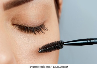 Beautiful Woman with long eyelashes in a beauty salon. Eyelash extension procedure. Lashes close up.Cosmetics and makeup.