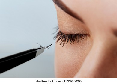 Beautiful Woman with long eyelashes in a beauty salon. Eyelash extension procedure. Lashes close up. Cosmetics and makeup. Close Up macro shot of fashion eyes visage.Cosmetics and makeup.