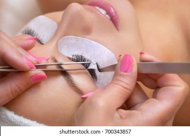 Schöne Frau mit langen Wimpern in einem Schönheitssalon. Eyelash-Verlängerungsverfahren. Nahaufnahme von Lashes