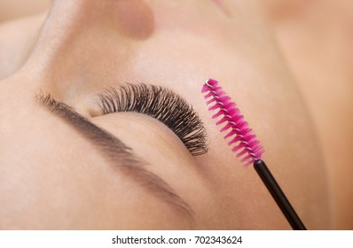 Beautiful Woman with long eyelashes in a beauty salon. Eyelash extension procedure. Lashes close up
