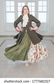 Beautiful woman in long green medieval dress and frock-coat dancing in the room