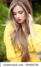 Beautiful woman with long hair. Fashion girl in summer park