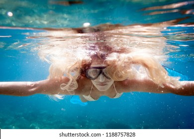 Beautiful woman with long hair underwater snorkeling in the tropical water