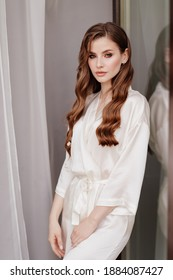 beautiful woman with long hair in a white robe at the window. the morning of the bride before the wedding. Natural beauty and professional make-up. beauticians and skin care products. natural light.