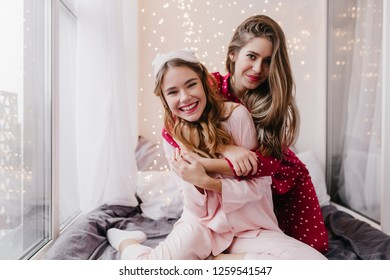 Beautiful woman with long hairstyle hugs with sister in weekend morning. Amazing white girl in eyemask enjoying joint photoshoot with friend.