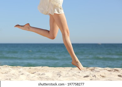 Beautiful woman long legs jumping on the beach with the sea in the background
