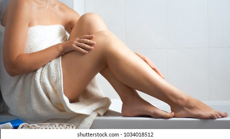 Beautiful woman with long legs relaxing in bath towel after bathing