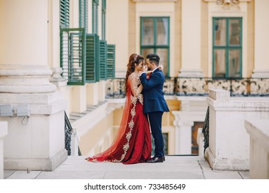Beautiful woman in a long red dress walks around the city with her husband in a blue suit and with a beard