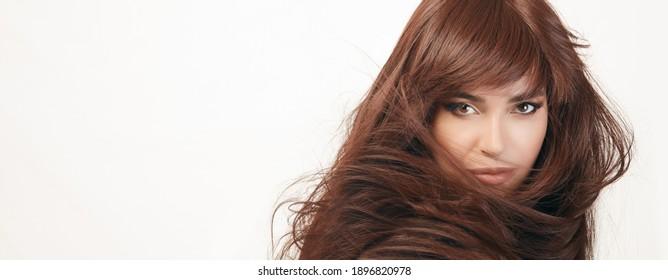 Schöne Frau mit langen glänzenden, gesunden Haaren fegte über ihre Schulter, einzeln auf Weiß mit Kopienraum in einem Haarpflegekonzept. Panorama-Schönheitsporträt einzeln auf Weiß