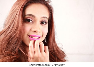 Beautiful woman with long straight hair and smile. Fashion model posing at studio.