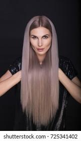 Beautiful woman with long straight trendy blonde hairs, studio shot.
