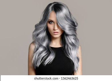 Beautiful woman with long wavy coloring hair. Flat gray background.