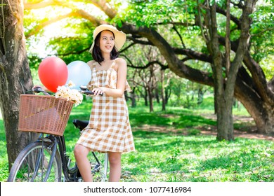 Beautiful woman look beautiful view at a nice park. Charming beautiful girl take a rest while gorgeous female rides a bicycle around a park. Lovely girl loves or admire nature, makes her clear brain