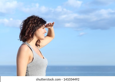 Beautiful woman looking ahead with the hand in forehead and the sea in the background