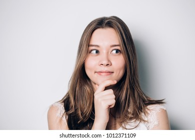 Beautiful woman looking aside holding hand under chin indenting to realize tricky plan. Attractive female having sly expression while looking aside