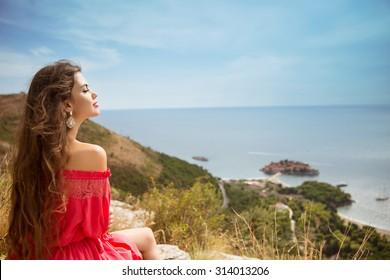 Beautiful woman looking in blue sky over Sveti Stefan island in Budva, Montenegro.
