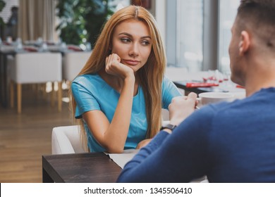 Beautiful woman looking bored at her date at the restaurant. Attractive woman looking unhappy and depressed over breakfast with her boyfriend. Breakup, relationship issues concept