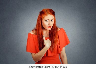 Beautiful woman looking at camera pointing with her finger to herself, you mean me gesture with hand isolated red background