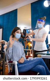 Beautiful woman looking at camera and showing ok while her hairdresser works on her hair